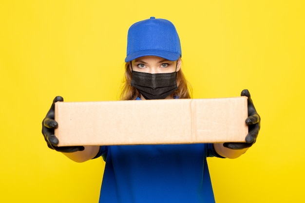 Une vue de face femme courier attrayant en polo bleu capuchon bleu et jeans holding package in black gants masque de protection noir sur le fond jaune job service alimentaire