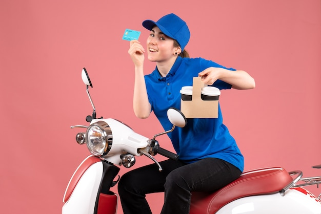 Vue de face femme courrier assis sur le vélo avec carte bancaire et café sur l'uniforme de couleur rose service de livraison emploi travailleur alimentaire