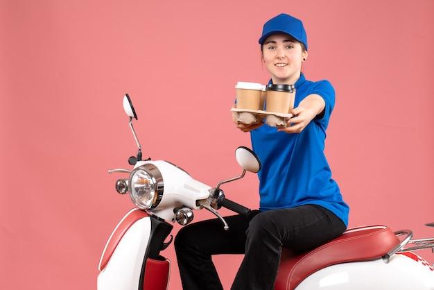 Vue de face femme courrier assis sur le vélo avec des tasses de café sur la livraison de nourriture de travail uniforme de couleur rose