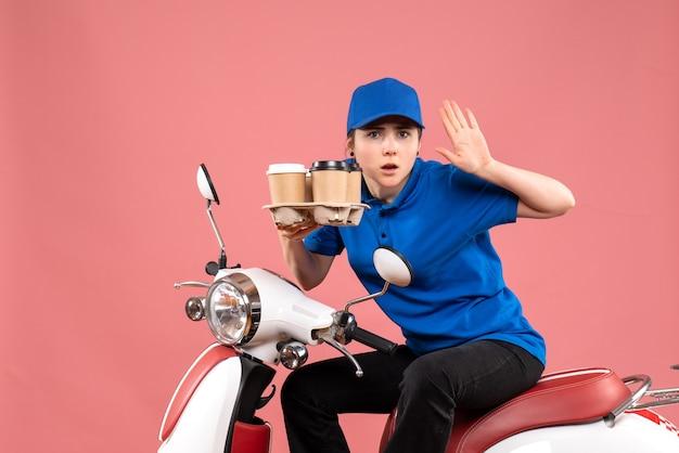 Vue de face femme courrier assis sur le vélo avec des tasses de café sur la livraison de service de travailleur uniforme de couleur de travail rose