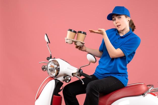 Vue de face femme courrier assis sur le vélo avec des tasses de café sur une livraison uniforme de couleur rose service alimentaire des travailleurs