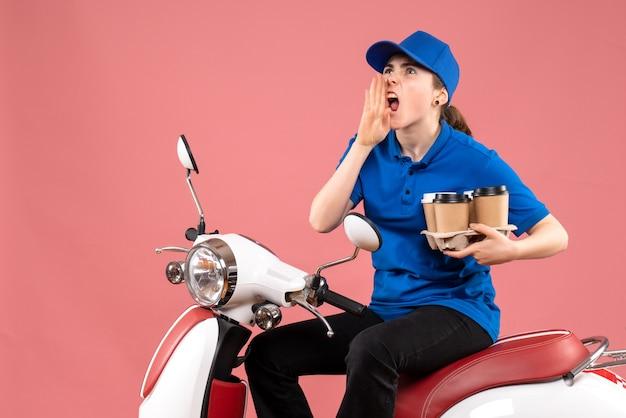 Vue de face femme courrier assis sur le vélo avec des tasses à café sur la livraison uniforme de couleur rose service alimentaire