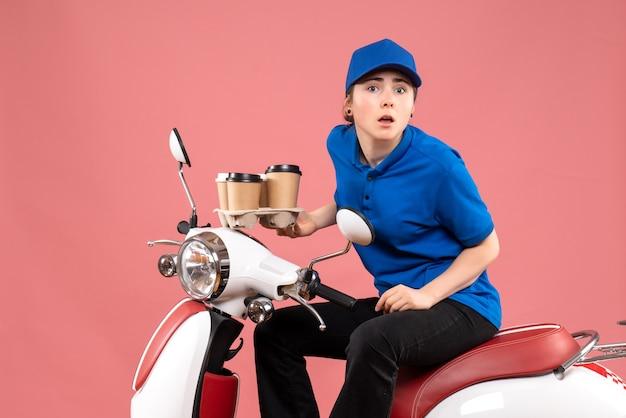 Vue de face femme courrier assis sur le vélo avec des tasses de café sur le travail de couleur rose service de livraison uniforme de travailleur