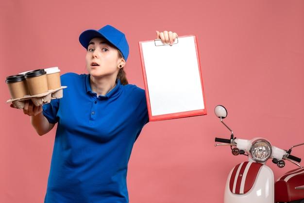 Vue de face femme courrier avec café de livraison et note de dossier sur le travail de livraison de travail rose travailleur de service uniforme de vélo