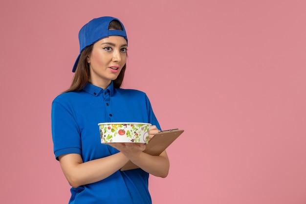 Vue de face femme courrier en cape uniforme bleu tenant le bloc-notes avec bol de livraison écrit des notes sur un mur rose clair, la prestation des employés de service