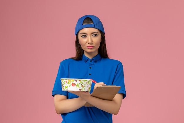 Vue de face femme courrier en cape uniforme bleu tenant le bloc-notes avec bol de livraison écrit des notes sur un mur rose clair, travail de livraison des employés de service