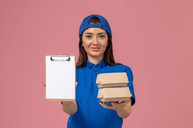 Vue de face femme courrier en cape uniforme bleu tenant le bloc-notes et petits colis de livraison sur le mur rose clair, la livraison des emplois de travail des employés de service