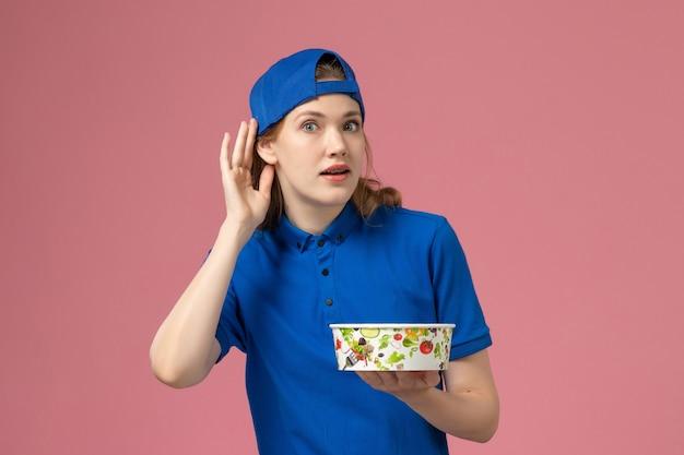 Vue de face femme courrier en cape uniforme bleu tenant le bol de livraison essayant d'entendre sur le mur rose, employé de la prestation de services