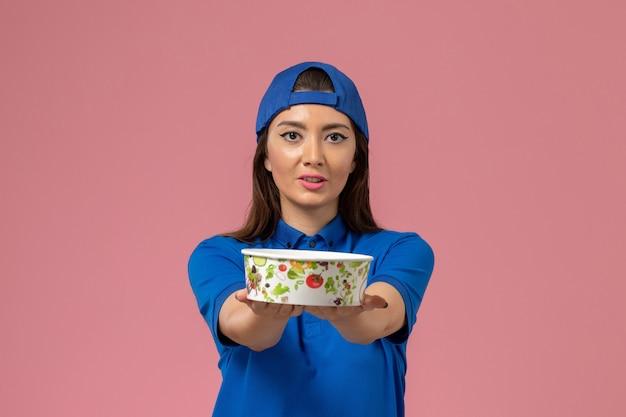 Vue de face femme courrier en cape uniforme bleu tenant le bol de livraison sur le mur rose clair, la livraison des employés de service