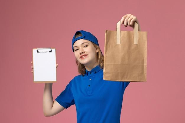 Vue de face femme courrier en cape uniforme bleu tenant le colis de livraison et le bloc-notes sur le mur rose, la livraison des emplois de service aux employés