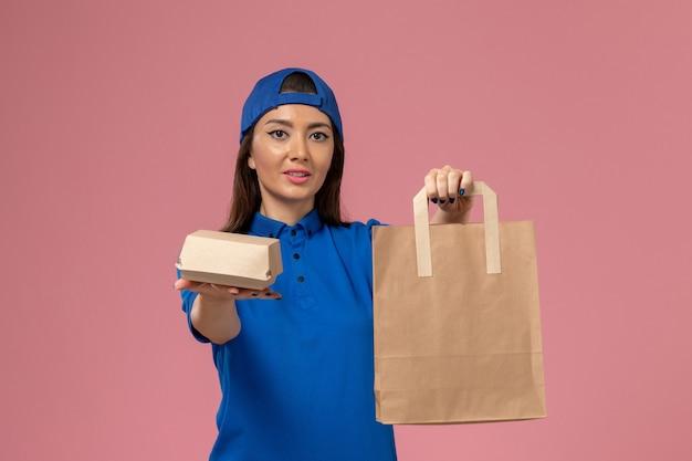 Vue de face femme courrier en cape uniforme bleu tenant différents colis de livraison sur le mur rose, employé de service offrant des emplois