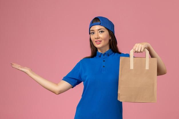 Vue de face femme courrier en cape uniforme bleu tenant le paquet de livraison de papier sur le mur rose clair, employé de service offrant des emplois
