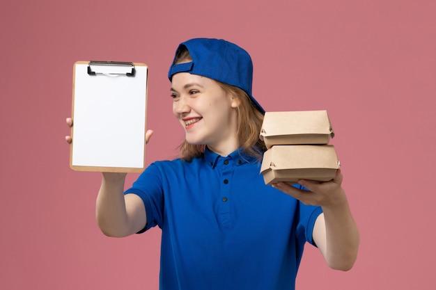 Vue de face femme courrier en cape uniforme bleu tenant peu de colis alimentaires de livraison et bloc-notes souriant sur fond rose employé du service de livraison