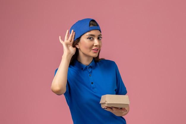 Vue de face femme courrier en cape uniforme bleu tenant peu de colis de livraison essayant d'entendre sur le mur rose
