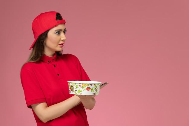 Vue de face femme courrier en cape uniforme rouge avec bloc-notes de bol de livraison ronde sur ses mains sur un mur rose clair, employé de livraison uniforme