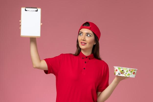 Vue de face femme courrier en cape uniforme rouge avec bloc-notes de bol de livraison ronde sur ses mains sur le mur rose clair, travail de l'employé de livraison uniforme