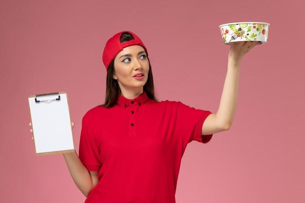 Vue de face femme courrier en cape uniforme rouge avec bloc-notes de bol de livraison ronde sur ses mains sur un mur rose clair, travailleur employé de livraison uniforme