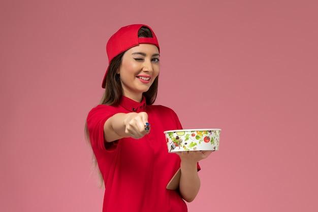 Vue de face femme courrier en cape uniforme rouge avec bloc-notes de bol de livraison ronde et stylo sur ses mains sur le mur rose clair, travail des employés de livraison uniforme