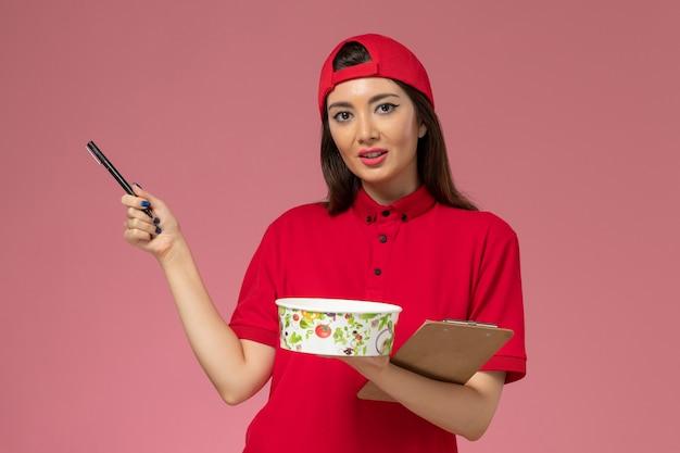 Vue de face femme courrier en cape uniforme rouge avec bloc-notes de bol de livraison ronde et stylo sur ses mains sur le mur rose clair, travail de travail employé de livraison uniforme