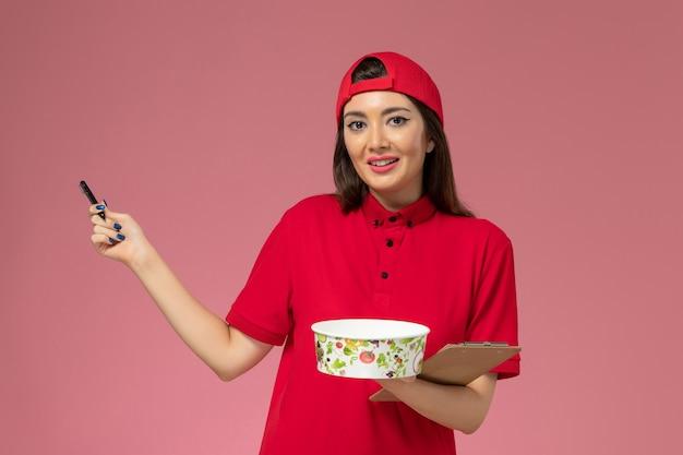 Vue de face femme courrier en cape uniforme rouge avec bloc-notes de bol de livraison ronde et stylo sur ses mains sur le mur rose clair, travail de travail des employés de livraison uniforme