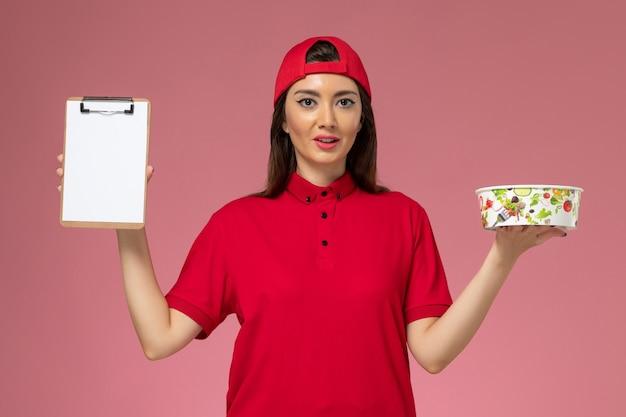 Vue de face femme courrier en cape uniforme rouge avec bol de livraison rond et bloc-notes sur ses mains sur le mur rose clair, employé de livraison uniforme