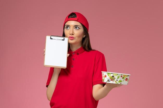 Vue de face femme courrier en cape uniforme rouge avec bol de livraison rond et bloc-notes sur ses mains en pensant sur le mur rose clair, employé de livraison uniforme