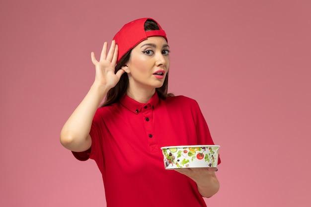 Vue de face femme courrier en cape uniforme rouge avec bol de livraison sur ses mains essayant d'entendre sur mur rose clair, employé de la prestation de services