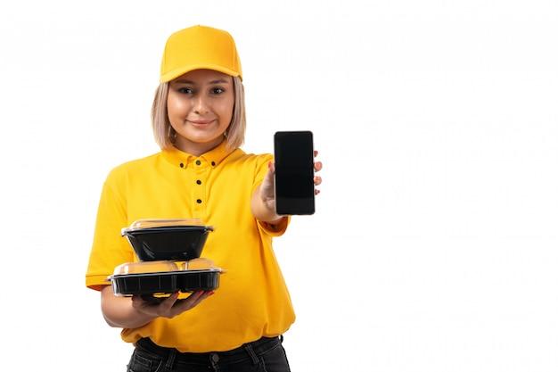 Une vue de face femme courrier en chemise jaune et bonnet jaune tenant des bols avec smartphone alimentaire souriant sur blanc