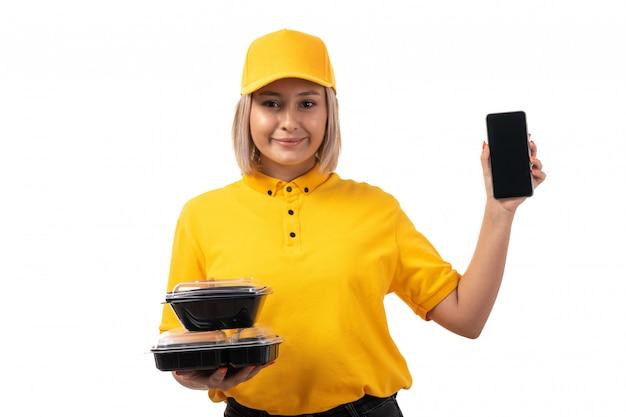 Une vue de face femme courrier en chemise jaune casquette jaune et jeans noirs tenant des bols avec de la nourriture et smartphone souriant sur blanc