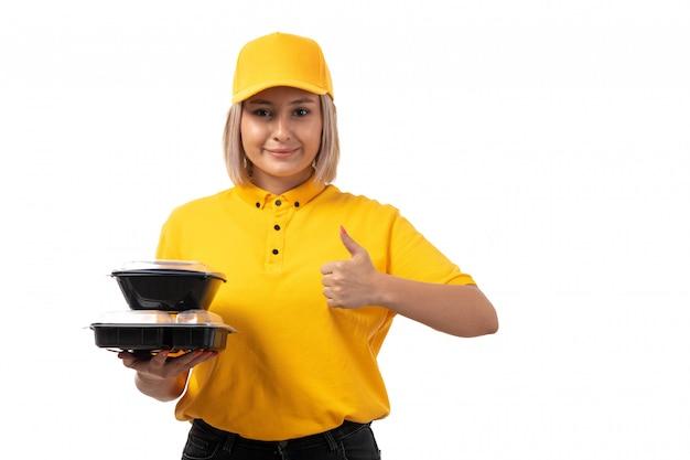 Une vue de face femme courrier en chemise jaune casquette jaune et jeans noirs tenant des bols avec de la nourriture souriant sur blanc