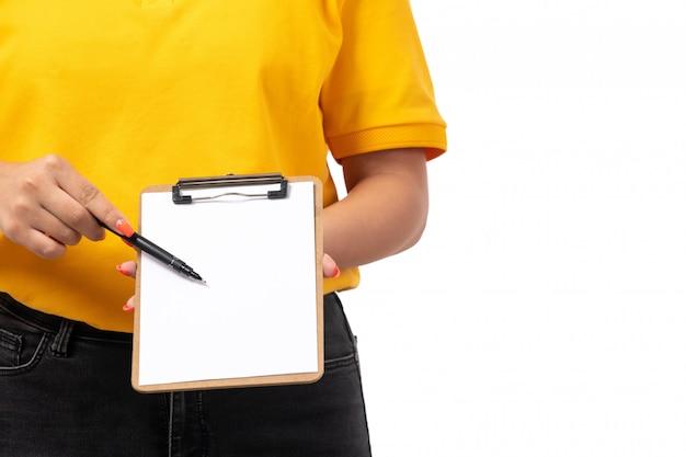 Une vue de face femme courrier en chemise jaune casquette jaune jeans noirs tenant du papier et un stylo sur blanc