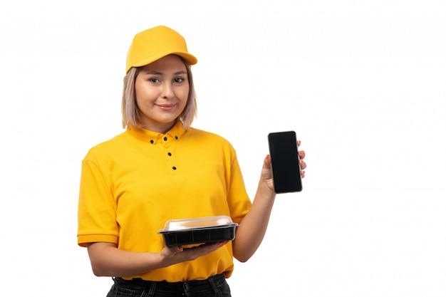 Une vue de face femme courrier en chemise jaune casquette jaune et jeans noirs tenant le smartphone et bol avec de la nourriture souriant sur blanc