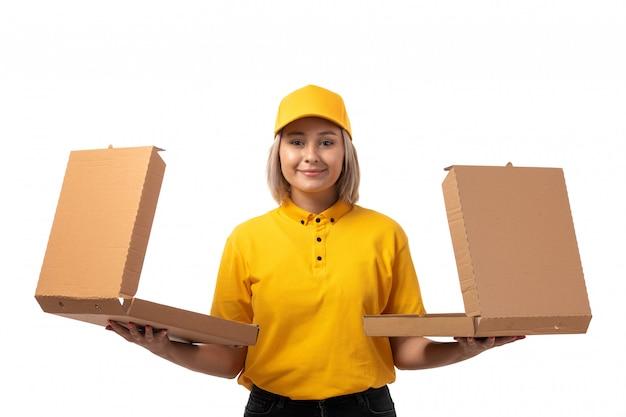 Une vue de face femme courrier en chemise jaune casquette jaune souriant tenant des boîtes sur blanc