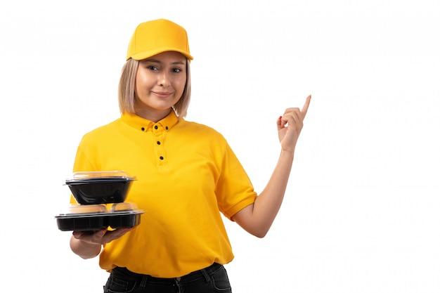 Une vue de face femme courrier en chemise jaune et casquette jaune tenant des bols avec de la nourriture sur blanc