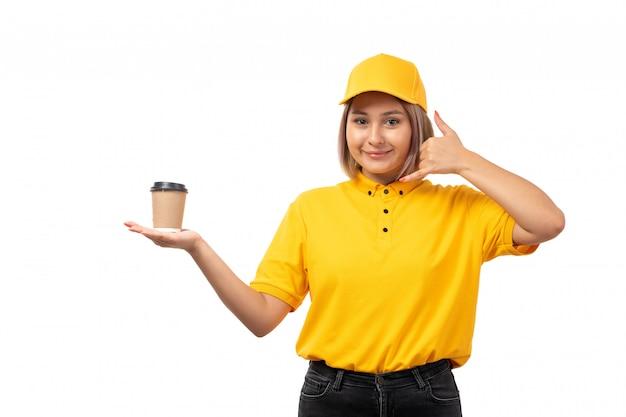 Une vue de face femme courrier en chemise jaune casquette yellwo et jean noir souriant posant tenant une tasse de café sur l'uniforme blanc
