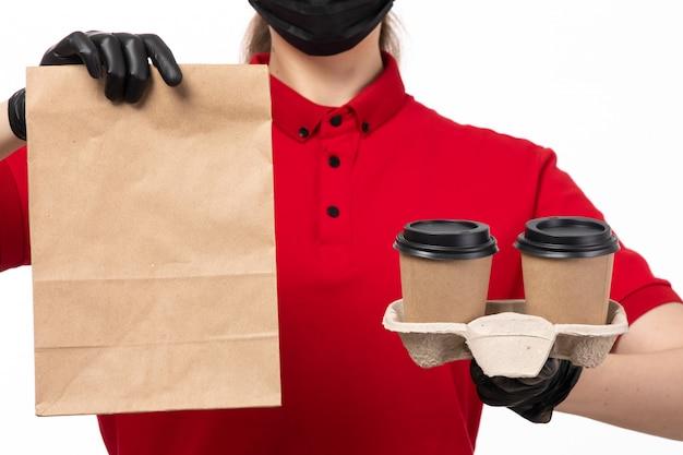 Une vue de face femme courrier en chemise rouge andb manque de glvoes tenant des tasses à café et de l'emballage avec de la nourriture