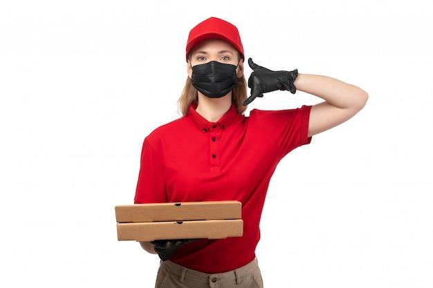 Une vue de face femme courrier en chemise rouge bonnet rouge gants noirs et masque noir tenant des boîtes à pizza sur blanc
