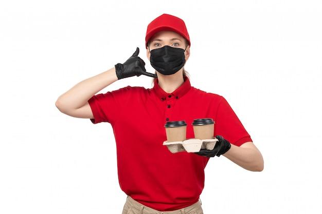 Une vue de face femme courrier en chemise rouge bonnet rouge gants noirs et masque noir tenant le café demandant d'appeler posant sur blanc