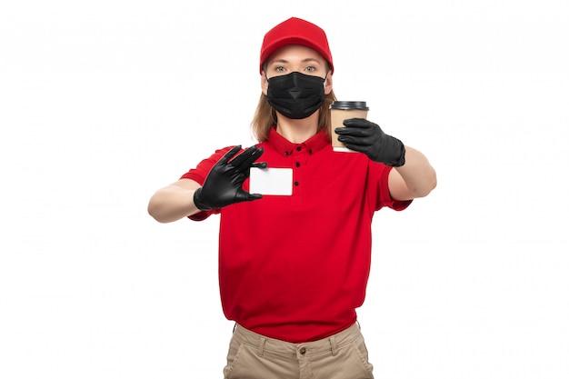 Une vue de face femme courrier en chemise rouge gants noirs bonnet rouge masque noir tenant café et carte blanche sur blanc