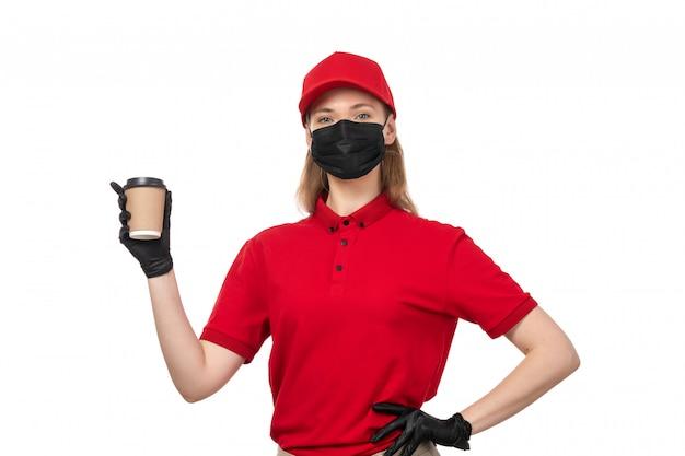 Une vue de face femme courrier en chemise rouge masque noir tenant une tasse de café