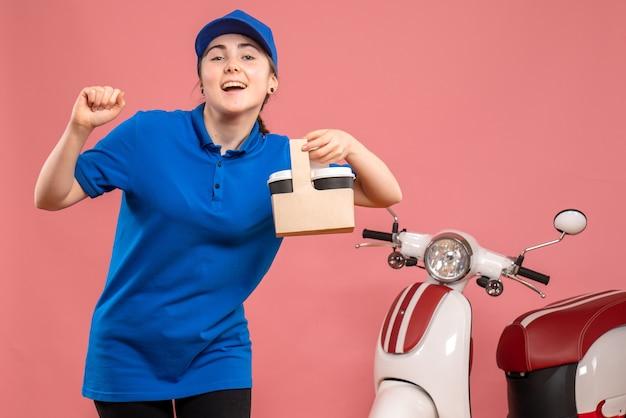Vue de face femme courrier avec livraison de café sur le service de livraison rose travailleur femme vélo uniforme travail