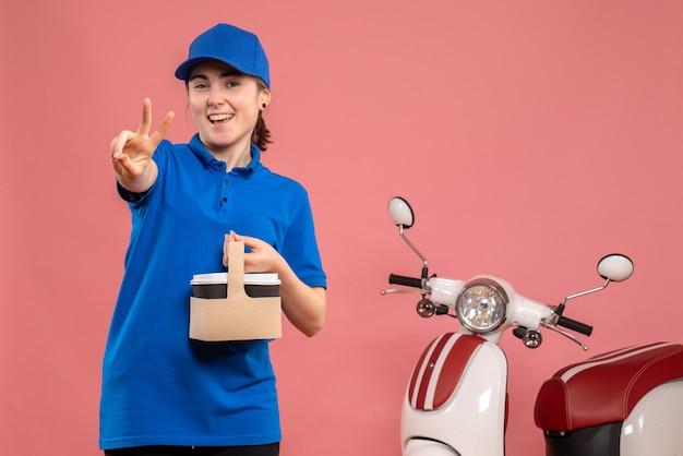 Vue de face femme courrier avec livraison de café sur le service de livraison de travail rose travail travailleur femme vélo uniforme