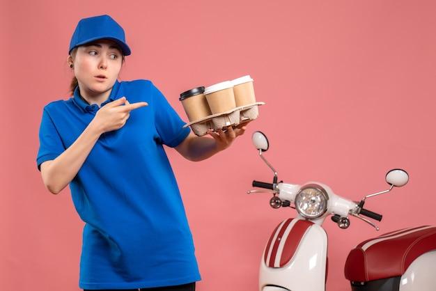 Vue de face femme courrier avec livraison de café sur le travail de livraison de travail rose vélo de service uniforme