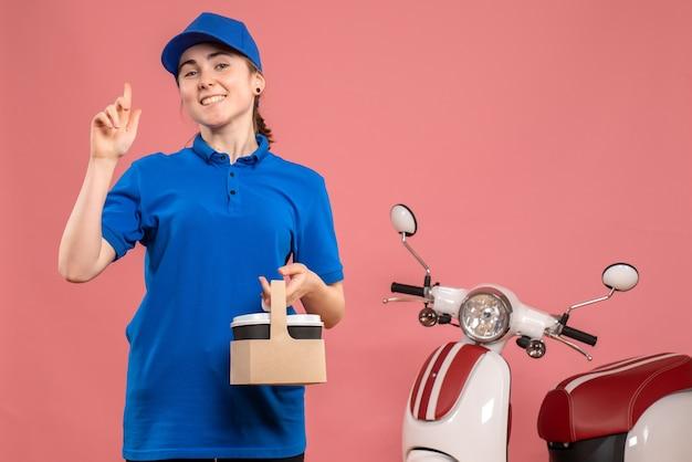 Vue de face femme courrier avec livraison de café sur l'uniforme de livraison de travail rose service travail femme vélo