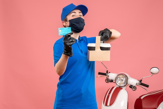Vue de face femme courrier en masque avec café de livraison et carte bancaire sur rose