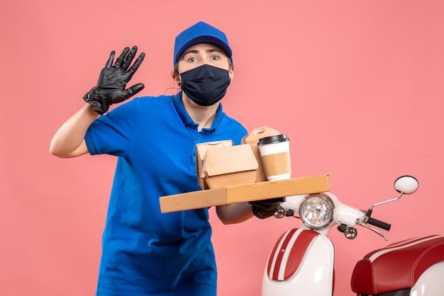 Vue de face femme courrier en masque avec livraison de café et de nourriture sur le rose