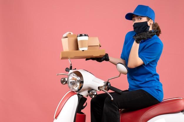 Vue de face femme courrier en masque avec livraison de nourriture sur le rose