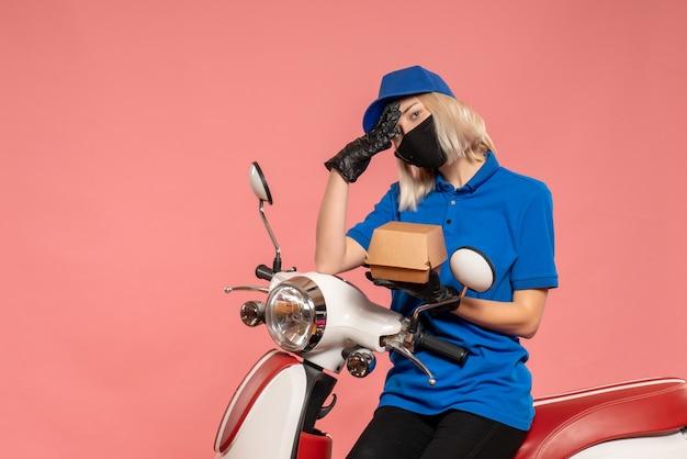 Vue de face femme courrier en masque avec petit paquet de nourriture sur le rose