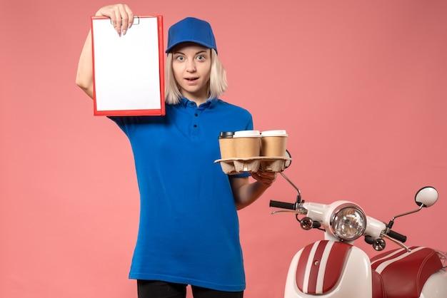 Vue de face femme courrier avec note de fichier et de livraison de café sur la couleur de travail uniforme de livraison de service d'emploi rose