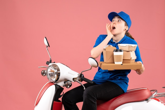 Vue de face femme courrier avec des paquets de nourriture et des boîtes sur le service d'uniforme de vélo de livraison de nourriture de couleur rose travailleur